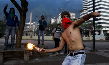 A  demonstrator throws an incendiary device during clashes with Venezuelan National Bolivarian Guard (GNB) during a protest against president Nicolas Maduro in Caracas, Venezuela. The<br />  Venezuelan government accuses the opposition of attempting a coup d'etat to topple President Nicolas Maduro, who narrowly won election last year as the hand-picked successor to left-wing populist Hugo Chavez, who died in office March 2013.