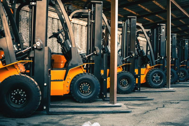 A fleet of parked forklifts.