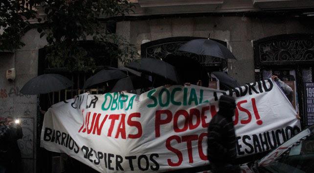 Activistas tapados con paraguas y una pancarta mientras abren la puerta del bloque en el número 33 de la calle Corredera Baja de San pablo, en Madrid.