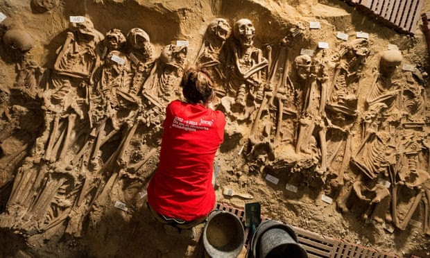 An archaeologist works at the site of eight mass graves found under a store in Paris. Scientists are carbon dating the remains and are carrying out DNA tests to establish how the people died. Photograph: Denis Gliksman/Inrap