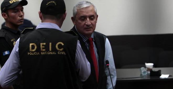 Otto Pérez Molina, custodiado por un policía, es trasladado a la cárcel del cuartel de Matamoros. - EFE