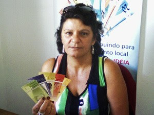 Maria Vani segura as notas de 'Comissari' no banco comunitário (Foto: Maria Vani de Caldas Villani/Arquivo Pessoal)