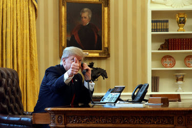 President Donald Trump gives a thumbs-up to reporters as he waits to speak by phone with the Saudi Arabia's King Salman in the Oval Office at the White House in Washington, U.S. January 29, 2017.