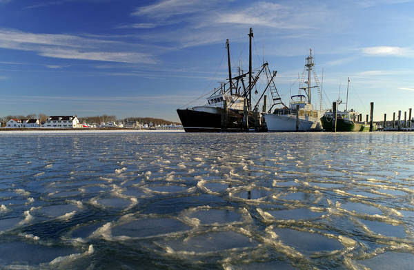 Surrounded by ice, commercial fishing boats are docked in their slips in Lake Montauk in Montauk, N.Y. earlier this year. (AP Photo/Julie Jacobson)