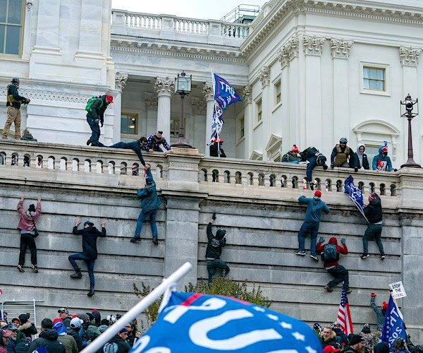 People climbing the walls of the Capitol