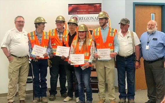 Graduates don orange safety vests and gold hardhats as they hold their certificates next to three staff members from the Regional Training Center.