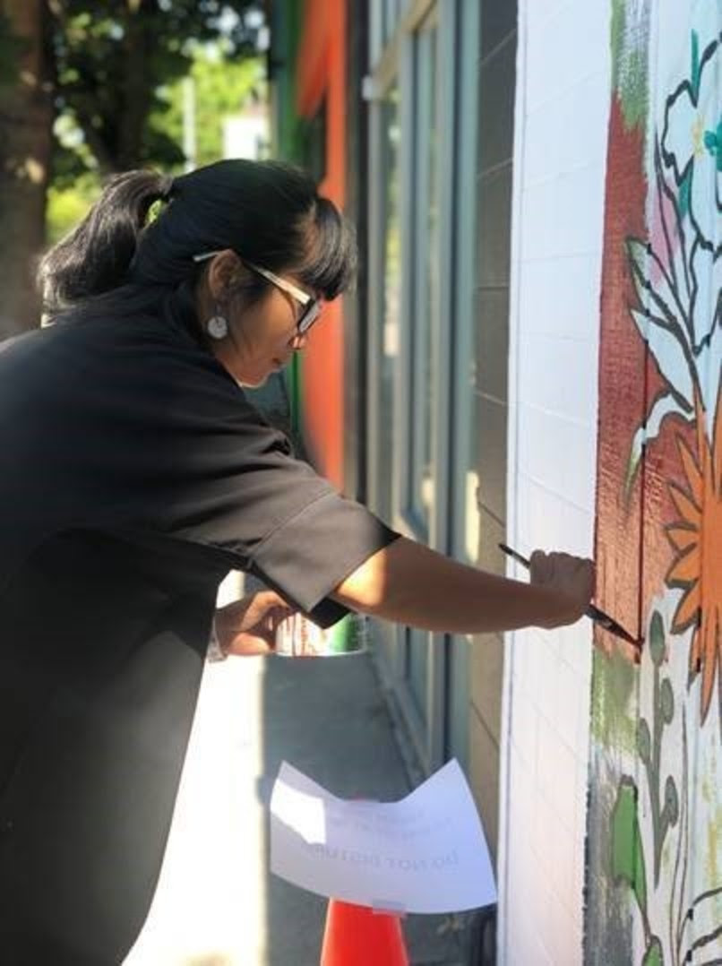 Image of artist Limei Lai holding a paintbrush as she works on painting a street mural