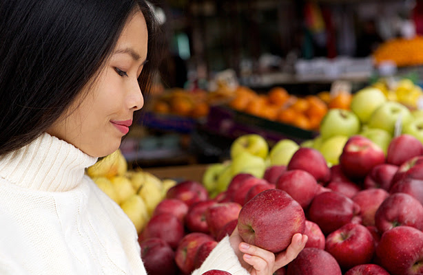 A young woman at the store looking at apples.