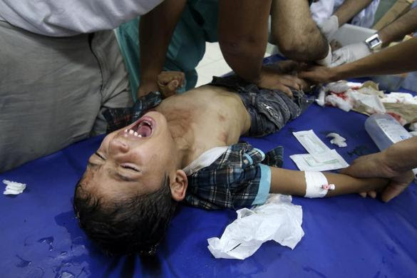 Palestinian medics tend to a boy who they said was wounded in an Israeli shelling, at a hospital, in Rafah in the southern Gaza Strip July 21, 2014. REUTERS-Ibraheem Abu Mustafa