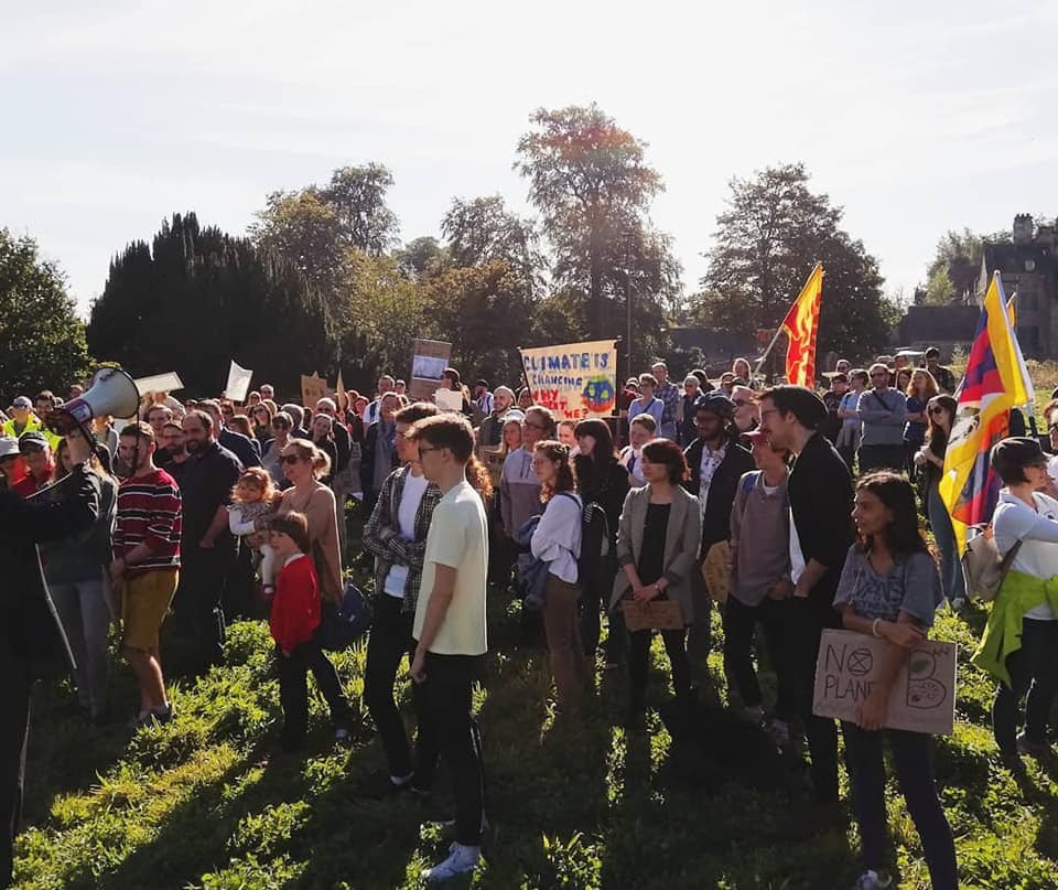 A group of 100+ strikers of all ages standing in a field in the sun, listening to a speech.