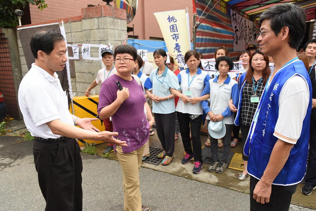 一名行政人員(圖中)欲前來上班,但工會以罷工為由勸阻離去。(攝影:宋小海)