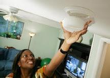 A woman installing a smoke alarm