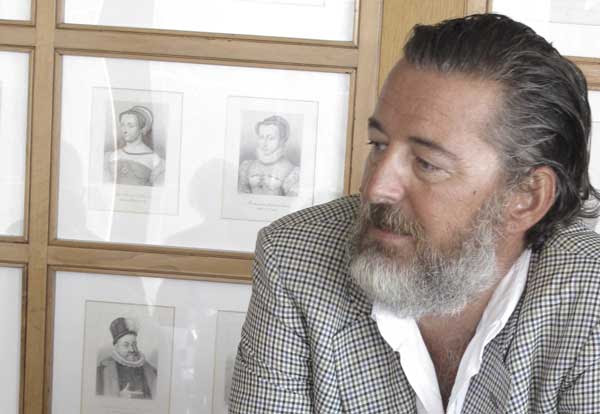 Photo of Sebastiano Rosa - producer of Barrua Isola dei Nuraghi IGT, 2016, showing his head and shoulders, informally dressed in an open white shirt and sports jacket looking to the left in front of a series of small lithographs of two women and one man.