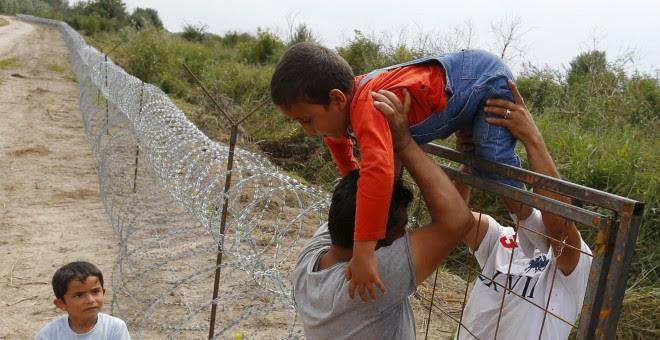Refugiados kurdos sirios pasan un niño sobre una cerca en la frontera húngaro-serbia, cerca Ásotthalom, Hungría .- REUTERS / Laszlo Balogh