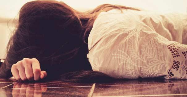 mujer recostada piso pensando deprimida