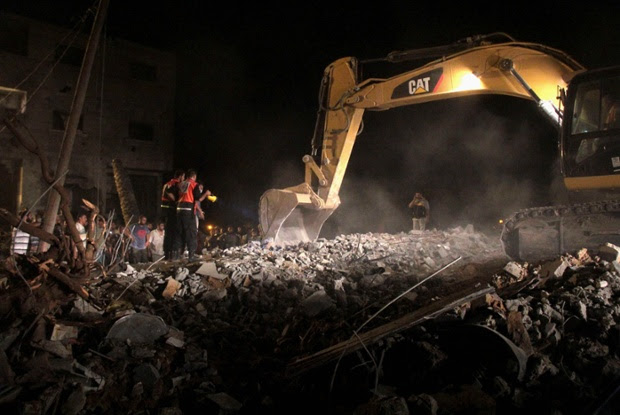 Palestinians search the for survivors amongst the remains of a family home in Gaza City.