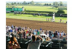 Spectators watch horses race on the turf at Keeneland