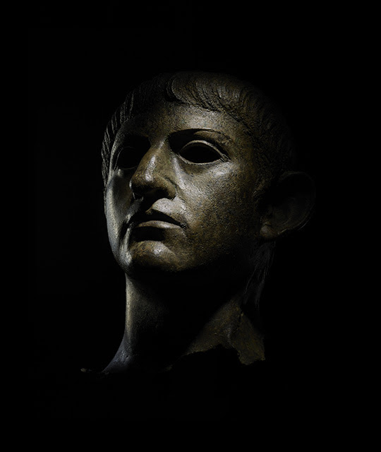 A bronze bust of the emperor Nero shown against a black background.