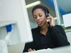 image of a woman in front of a computer with a headset on