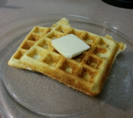 Waffles on the plate with butter and syrup. Just a little syrup for me!
