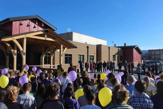 A crowd stands outside the front of the new Pine Bluffs Elementary School during the ribbon cutting ceremony, including the school children, who are holding purple and yellow balloons.