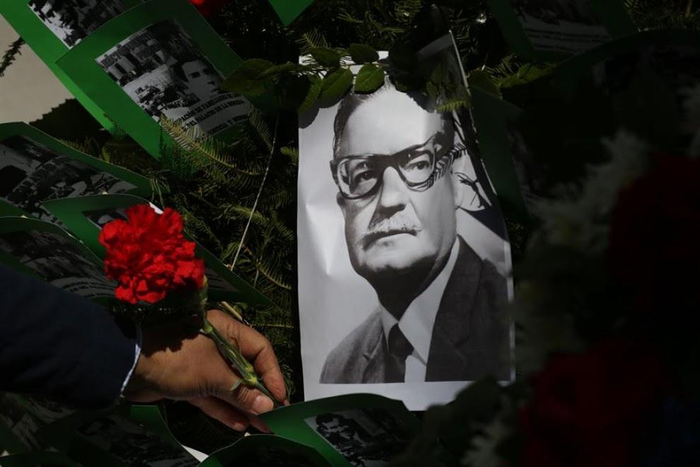 Un hombre deja una flor sobre la imagen del presidente chileno Salvador Allende, este viernes en Santiago. Chile conmemora el 47 aniversario del golpe de Estado de Augusto Pinochet, que derrocó al Gobierno de Salvador Allende, en plena pandemia de corona
