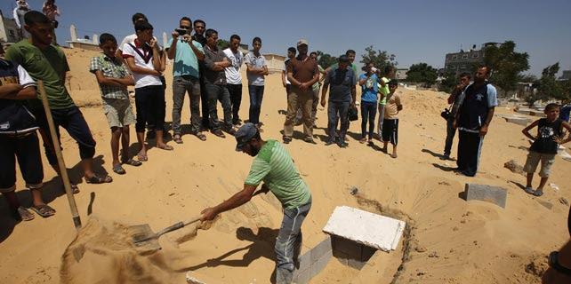 Palestinos preparan una tumba para enterrar los cuerpos de la mujer del líder de Hamas y su hijo Ali, muertos por los ataques de Israel de este martes, tras la suspensión de la tregua. REUTERS/Mohammed Salem