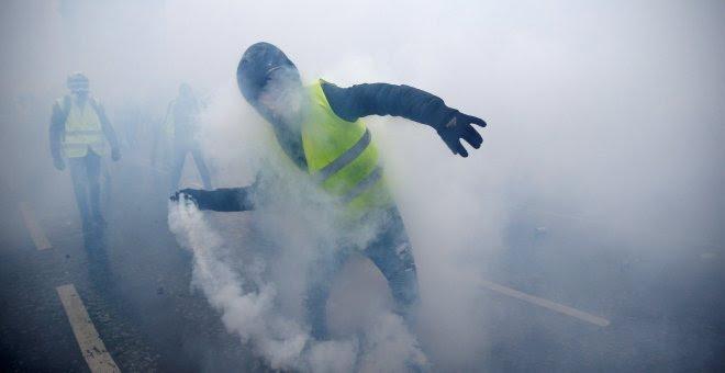 Un hombre, ataviado con un chaleco amarillo, lanza una granada de gas lacrimógeno.- Stephane Mahe/REUTERS