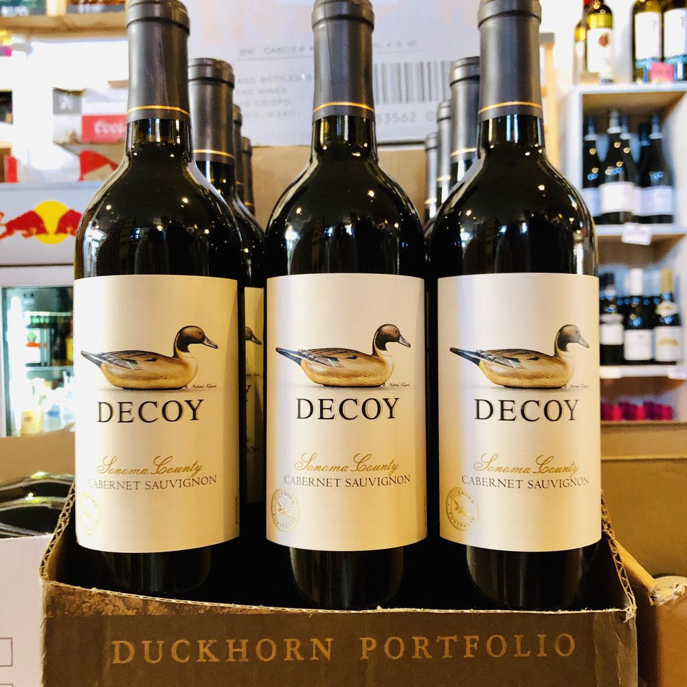 A display case showing 12 bottles of Duckhorn's Decoy Cabernet Sauvignon.