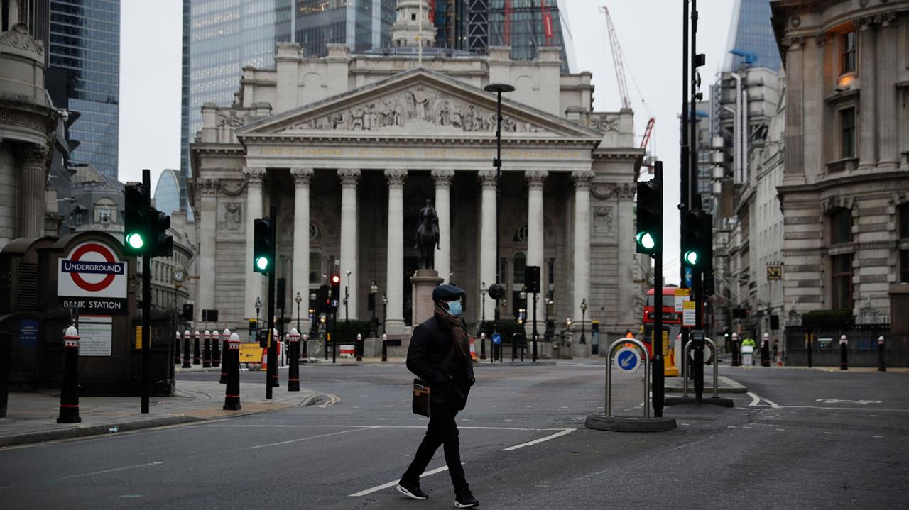 A man crosses the street backdropped by the Royal Exchange in the City of London financial district in London, Jan. 5, 2021, on the first morning of England entering a third national lockdown.
