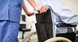 Image of nurse pushing patient in wheelchair