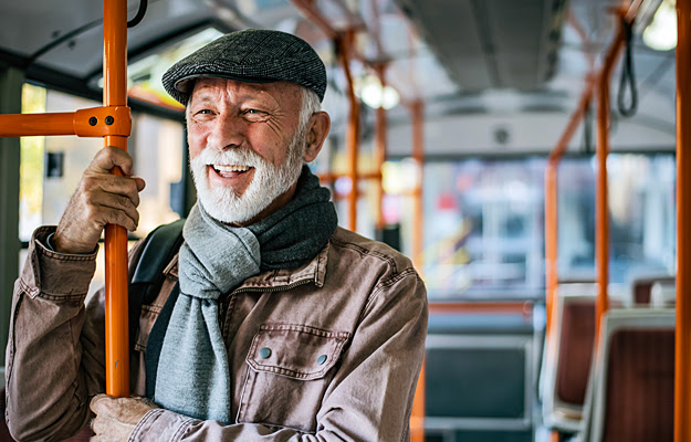 A senior man riding a public bus.