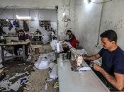 Palestinians manufacture protective coverall suits in a small sewing factory in Gaza City, 30 March 2020