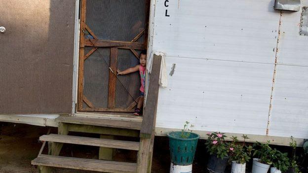Criança na porta de uma casa pobre