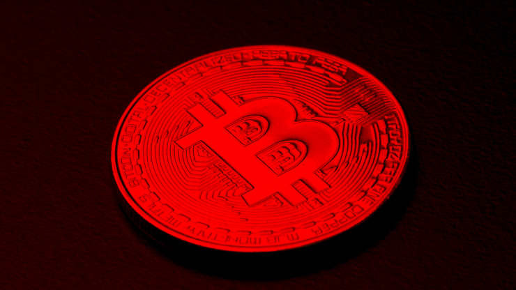 A coin with the letter ''B'' on it is cast in a red light