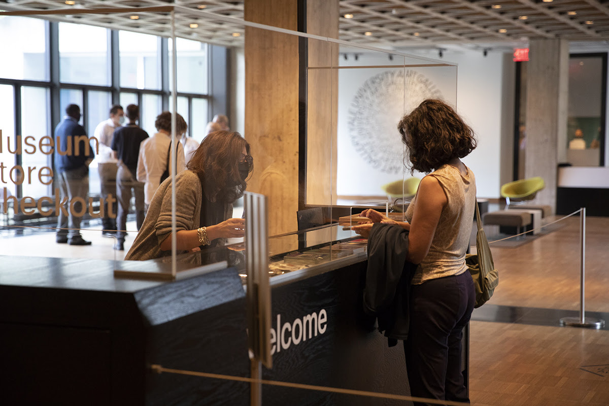 visitor checking in at the Welcome desk in the Gallery's lobby