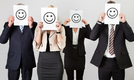 """Photo of employees holding up """"happy faces"""" signs"""