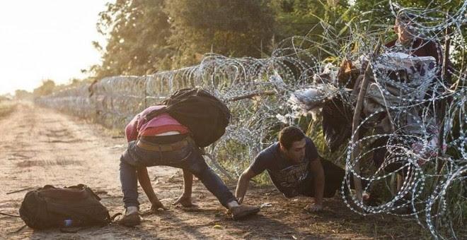 Varios refugiado pasan la alambrada en la frontera entre Hungría y Serbia cerca de Roszke (Hungría). / SANDOR UJVARI (EFE)