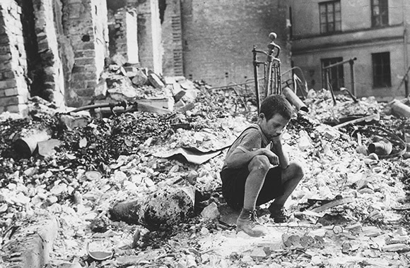 A young boy sits among the ruins of his home in Warsaw after it was destroyed during a German air raid.