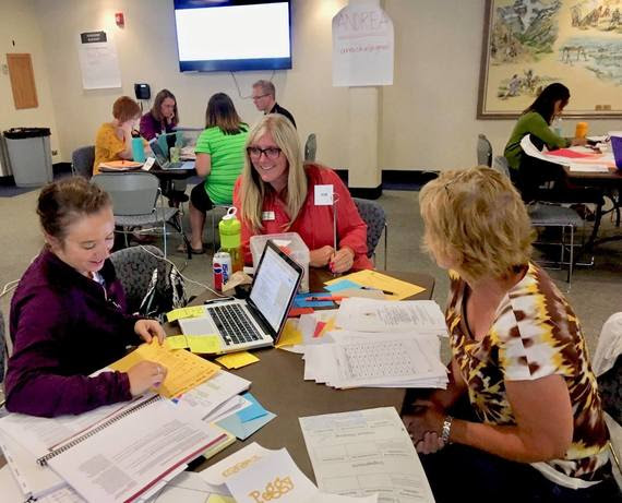 A WDE employee sits with two teachers at a table developing agriculture focused curricula for Wyoming's science standards.