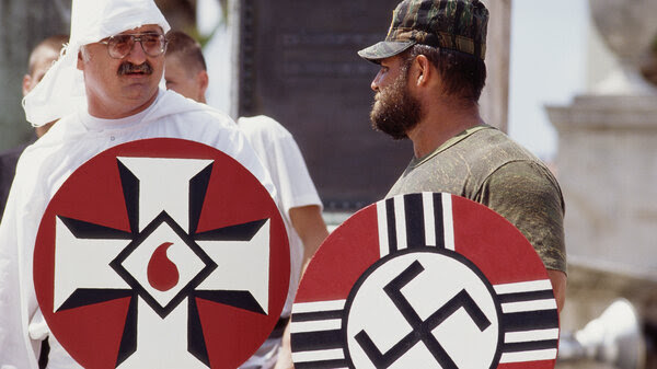 An undated photo shows a Ku Klux Klansman and Neo-Nazi demonstrator holding symbolic shields at a march in Palm Beach, Fla. In Bring the War Home, author Kathleen Belew argues that America's disparate racists groups came together after the Vietnam War.