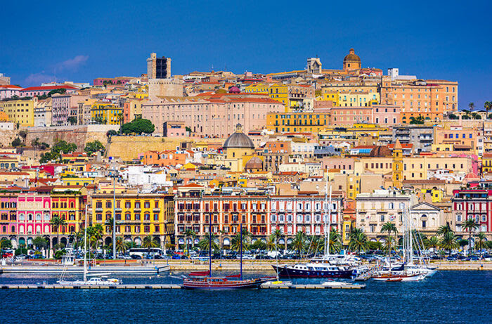 A deliciously inviting photo of a seaside town in Sardinia, shot from the ocean, showing a placid, blue water, sailing boats with sails furled in the foreground, beautifully coloured buildings rising up the hillside topped by a brilliant, bright, blue sky.