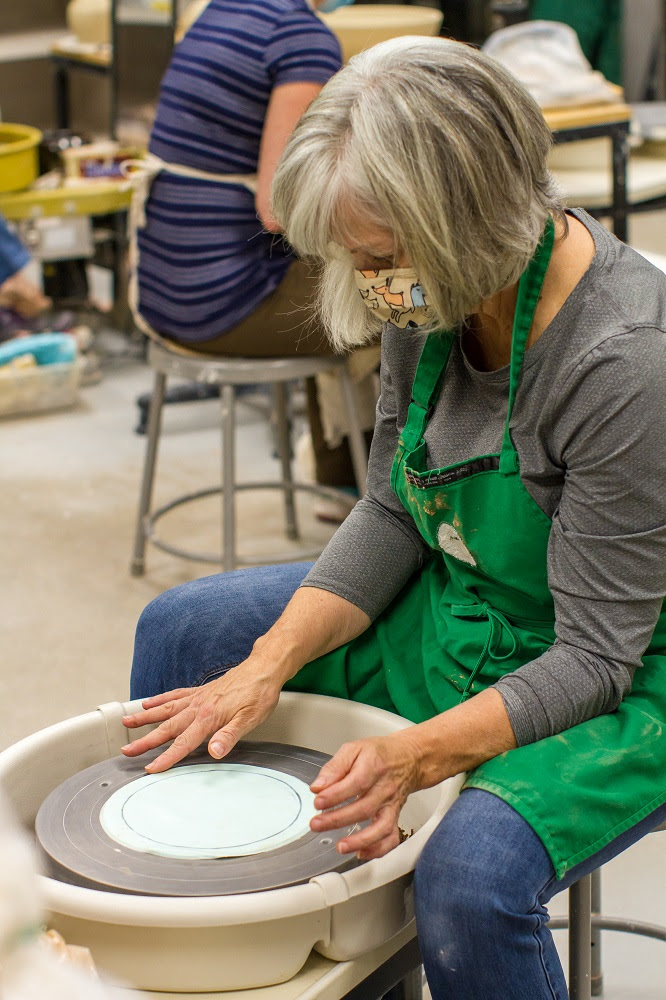 A white woman with grey hair sits at a pottery wheel