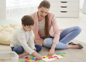 A speech-language pathologist leads a speech-language therapy session with a young boy.