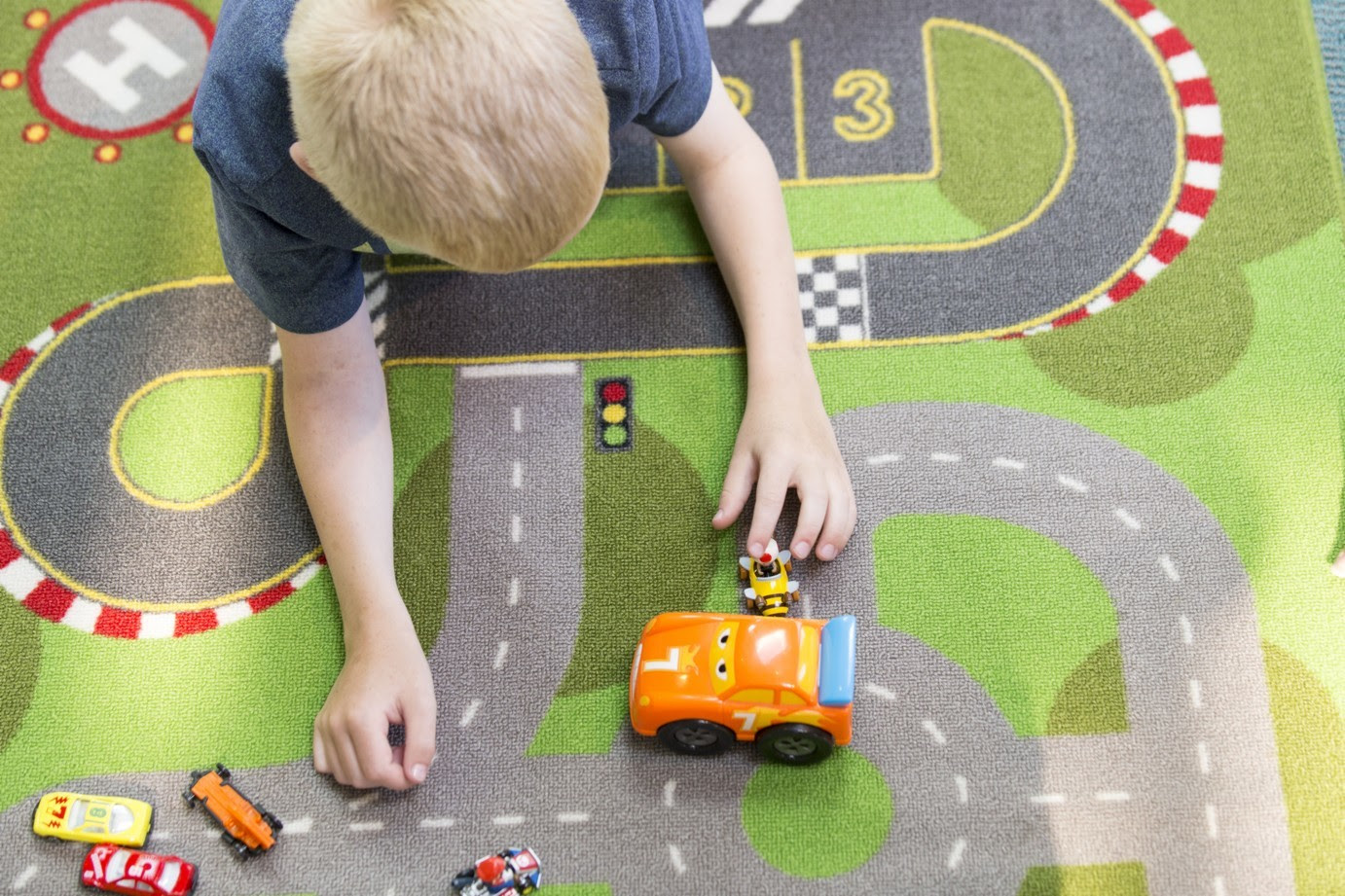 child playing with cars