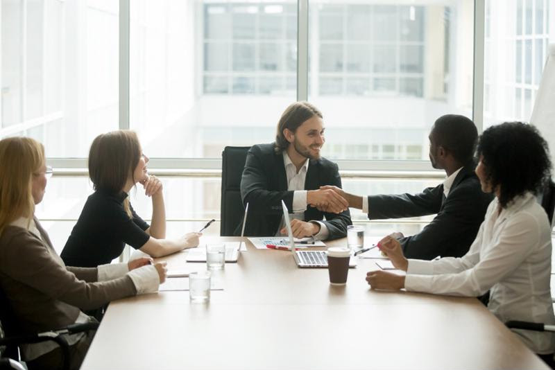 Employees shake hands in a boardroom.