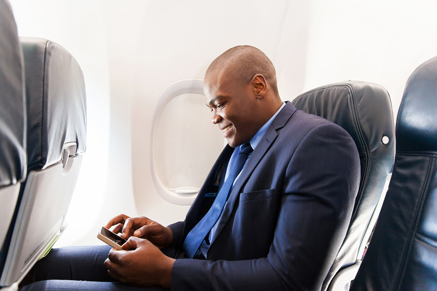 happy african airplane passenger using smart phone on plane