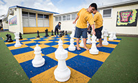 Children playing giant outdoor chess