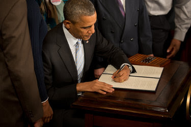 President Obama signing an executive order in February 2014 directing federal contractors to raise their minimum wage for federally funded workers.
