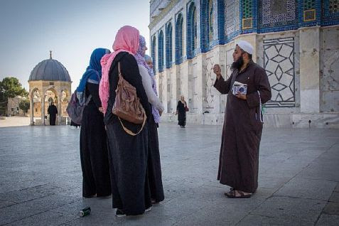 Muslim man speaking with a group of women at the Dome of the Rock mosque on the Temple Mount.